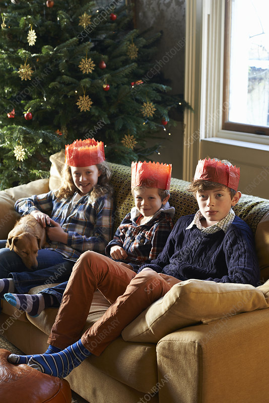Children in paper crowns sitting on sofa