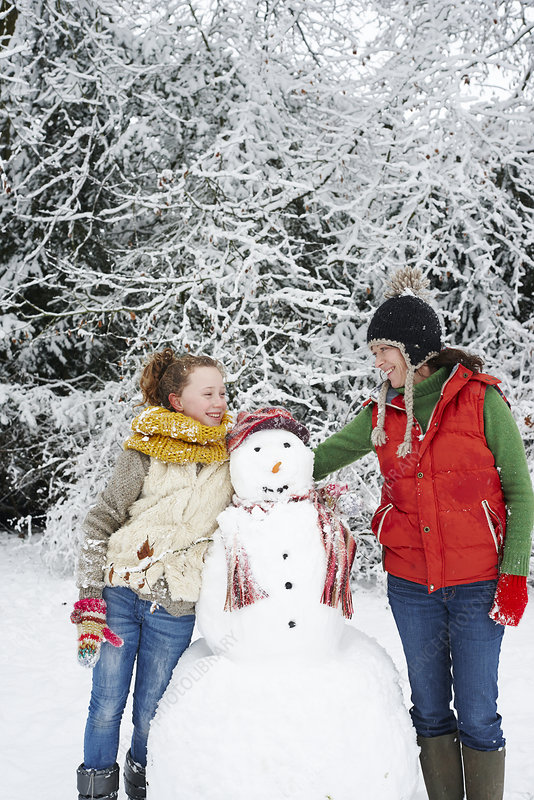 Mother and daughter with snowman