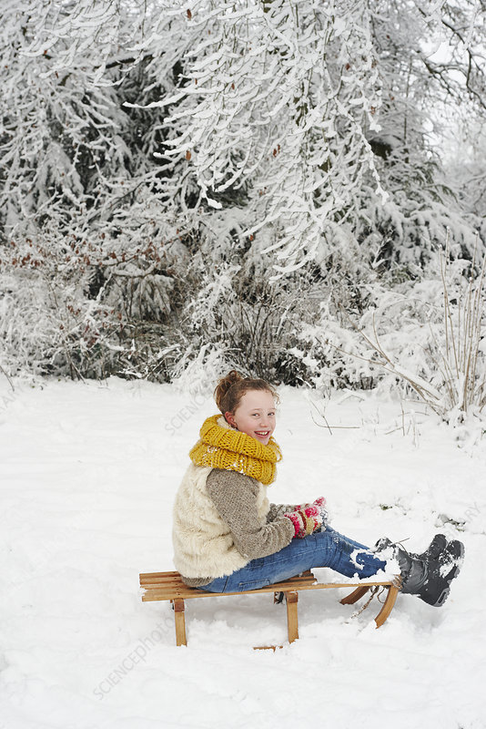 Girl sitting on wooden sled in snow