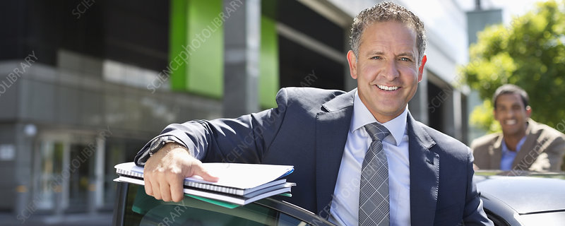 Businessman climbing out of car