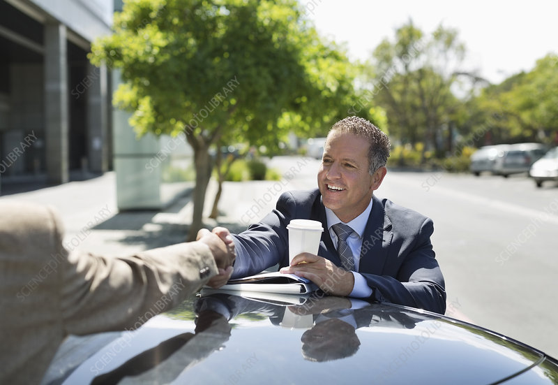 Businessmen shaking hands over car