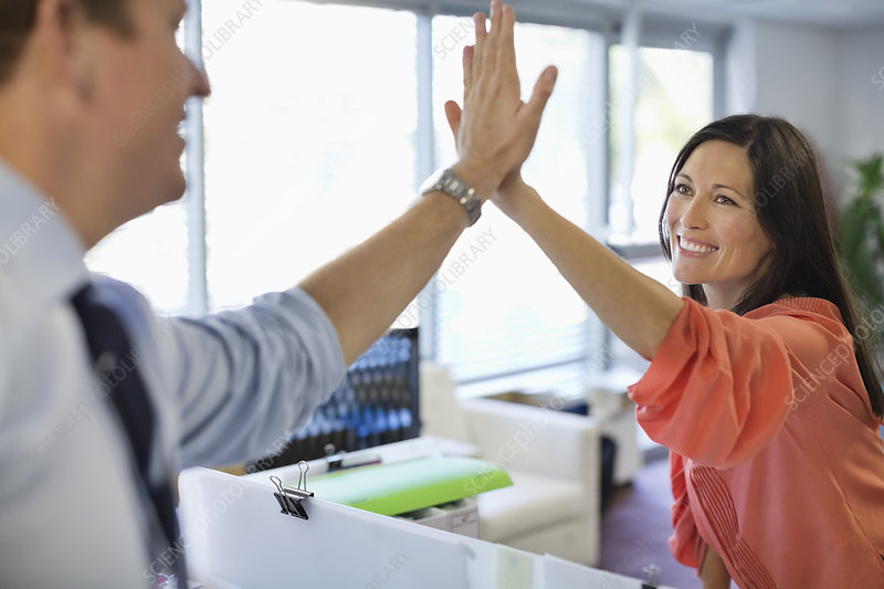 Business people high fiving in office