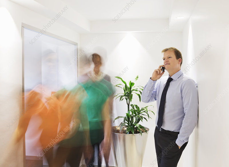 Businessman on cell phone in busy hallway