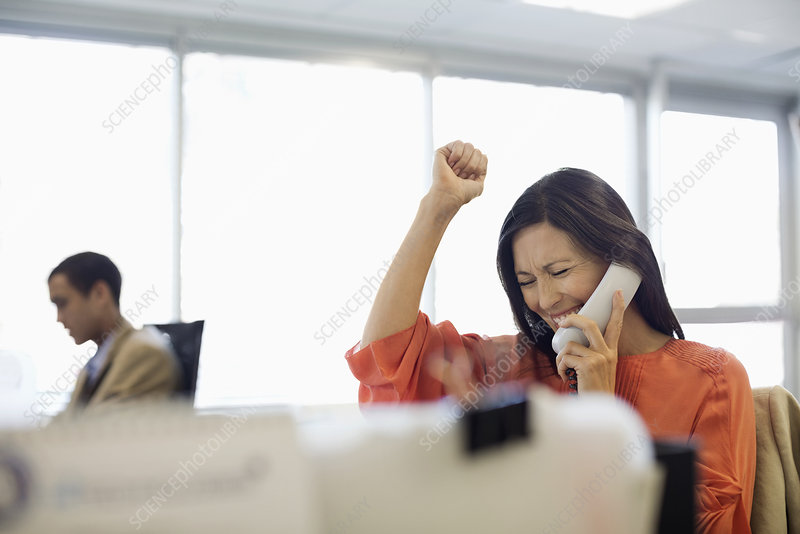 Businesswoman cheering at desk in office