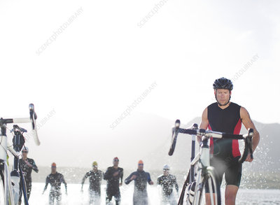 Triathletes emerging from water,