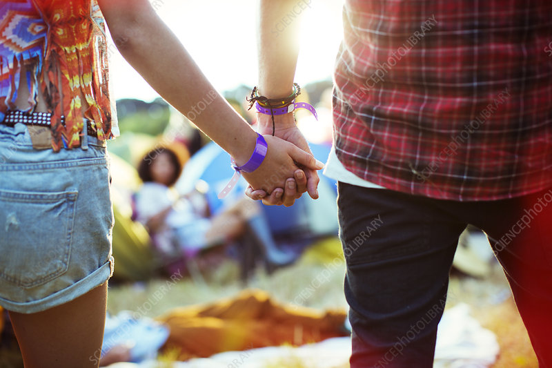 Couple holding hands outside tents