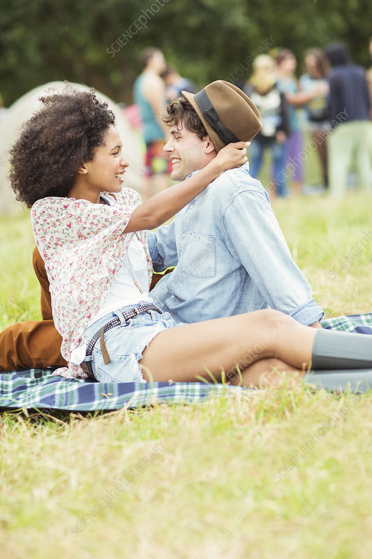 Couple hugging on blanket in grass