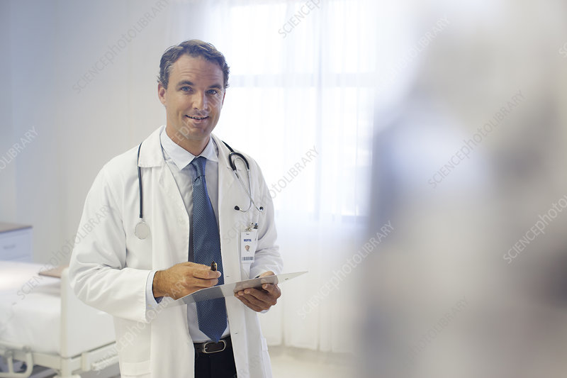 Doctor reading clipboard in hospital room
