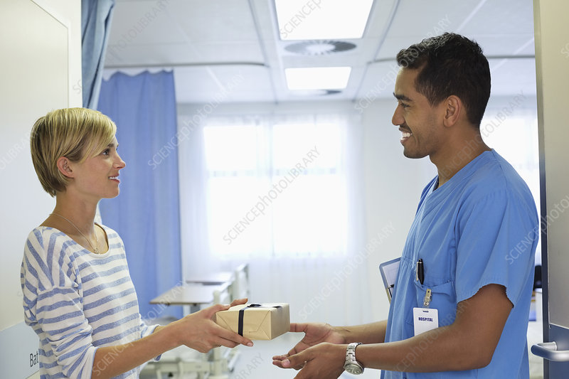 Patient giving nurse gift in hospital