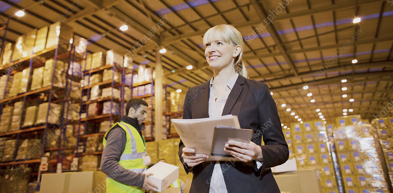 Businesswoman smiling in warehouse
