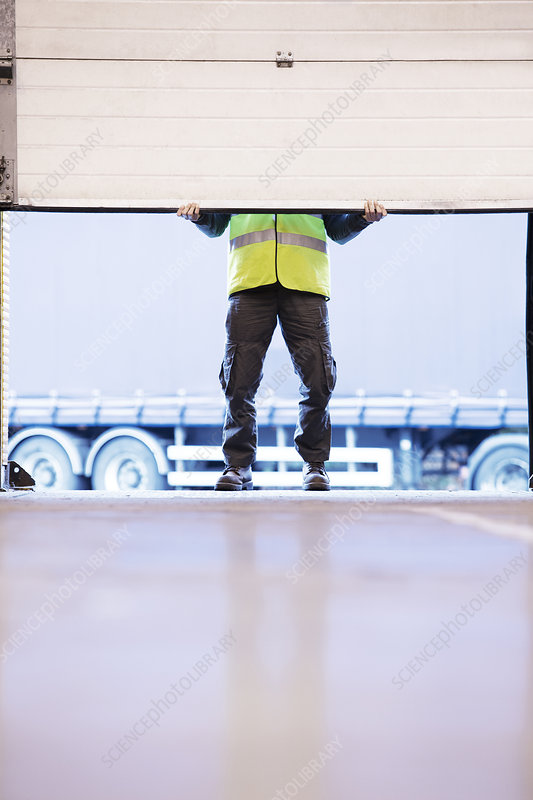 Worker lifting door in warehouse