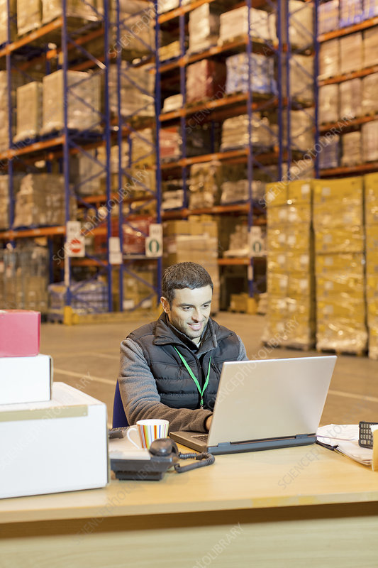 Worker using laptop in warehouse