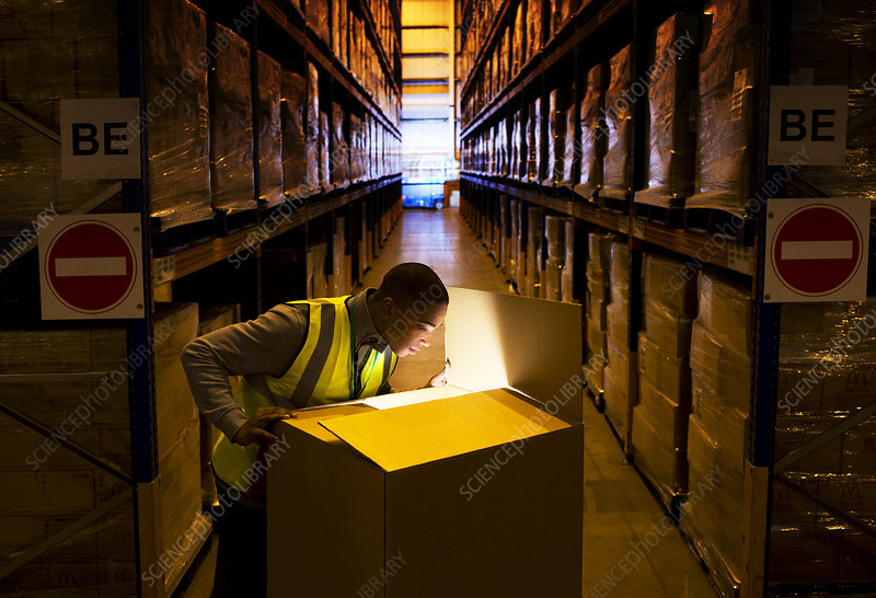 Worker opening glowing box in warehouse