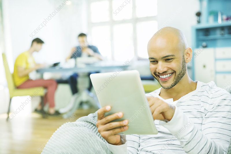 Man using tablet computer in living room