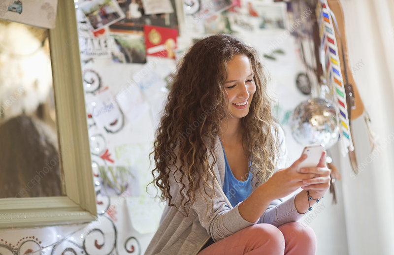 Woman using cell phone in bedroom