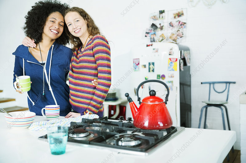 Women hugging in kitchen
