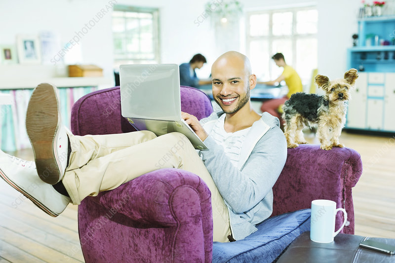 Man using laptop in armchair