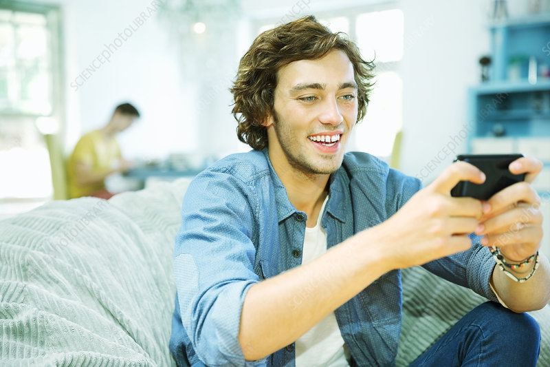 Man using cell phone in beanbag chair