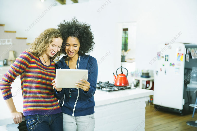 Women using tablet computer in kitchen