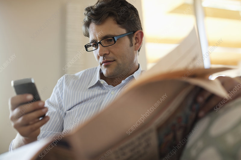 Man using cell phone and reading