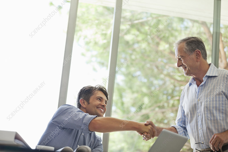 Men shaking hands in living room