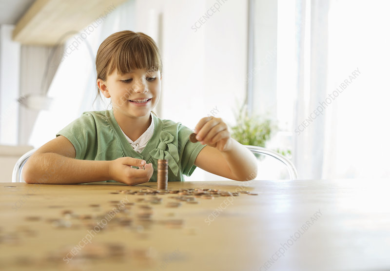 Girl stacking pennies on counter
