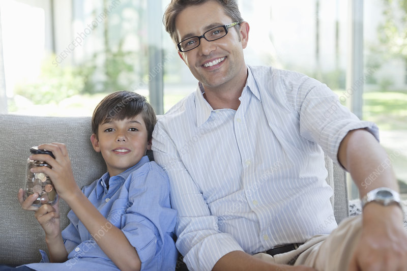 Father and son with change jar on sofa