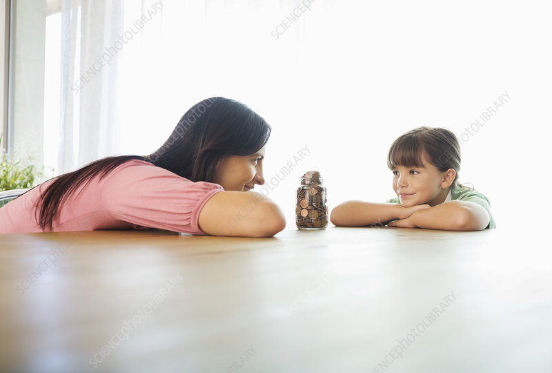 Mother and daughter with change jar