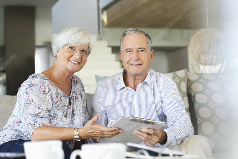 Older couple reading clipboard on sofa