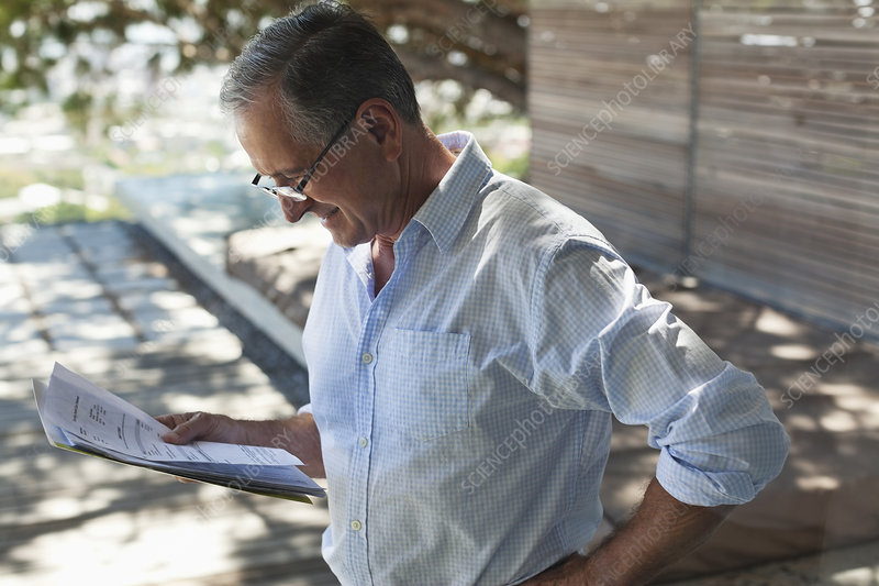 Businessman reading papers outdoors