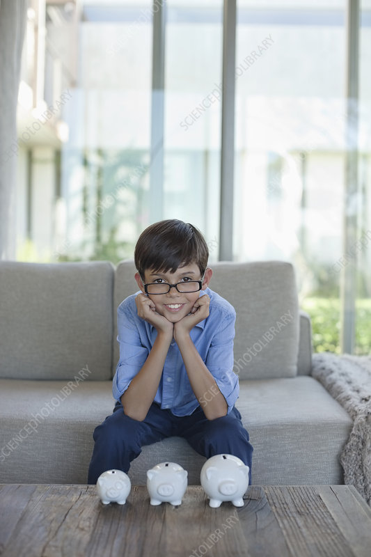 Boy examining piggy banks on coffee table