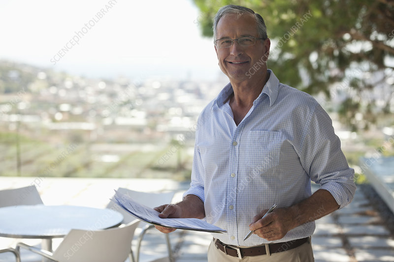 Older man reading papers outdoors