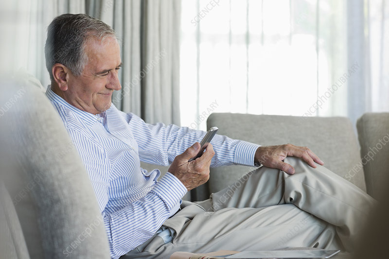 Older man using cell phone on sofa