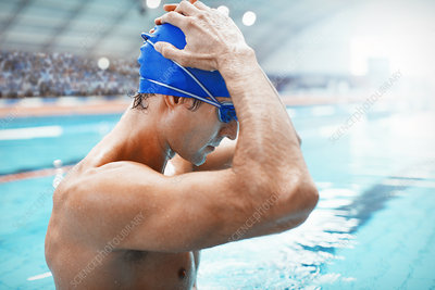 Swimmer adjusting cap at poolside