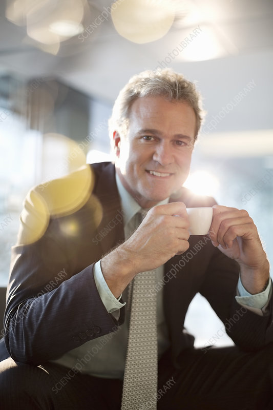 Smiling businessman drinking espresso