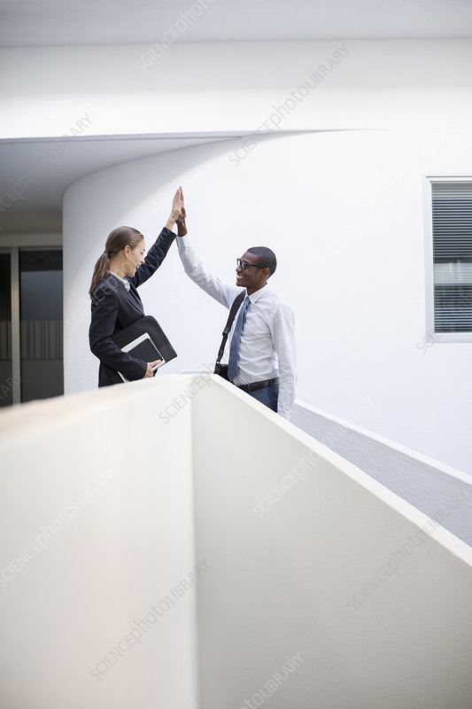 Businessman and businesswoman high fiving