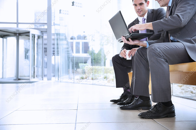 Businessmen sharing laptop in lobby