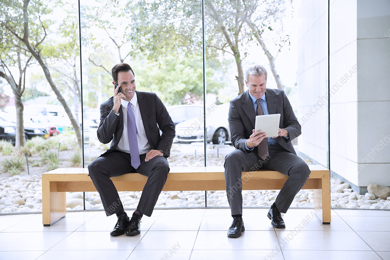 Businessmen using cell phone and tablet