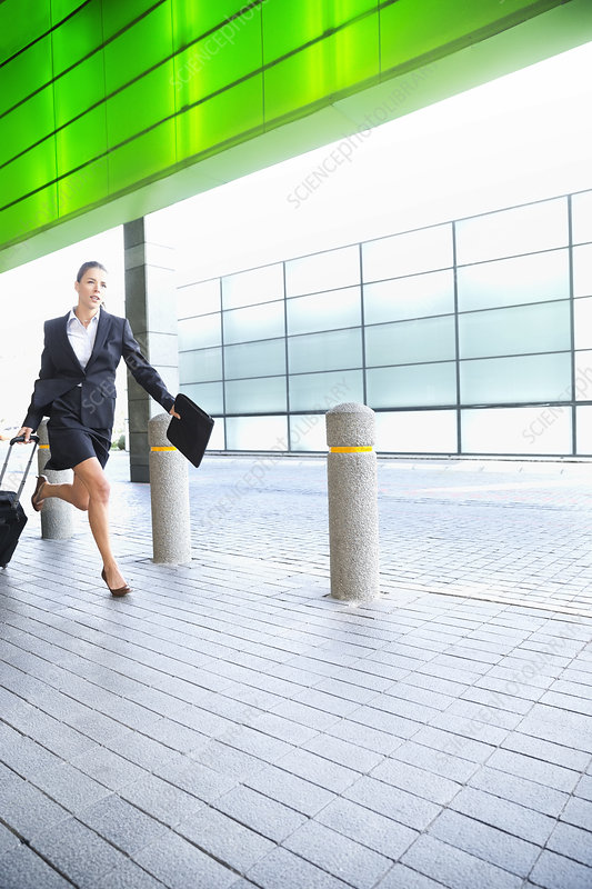 Businesswoman running with suitcase
