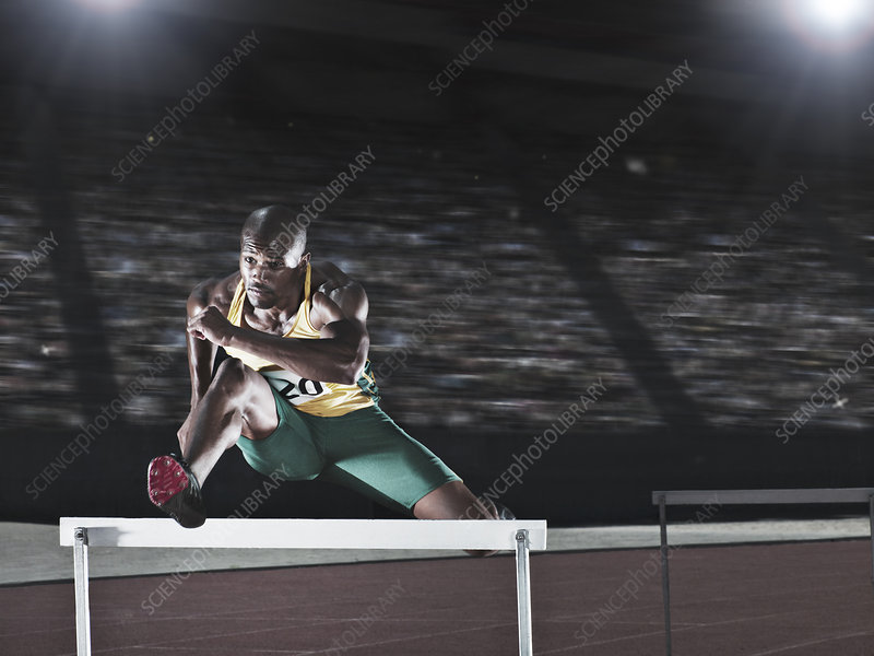 Runner jumping hurdle on track