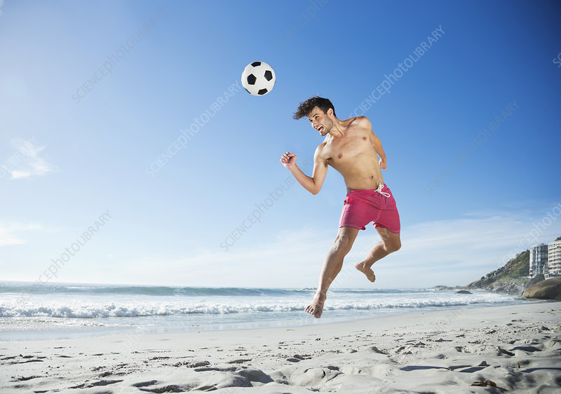 Man heading soccer ball on beach