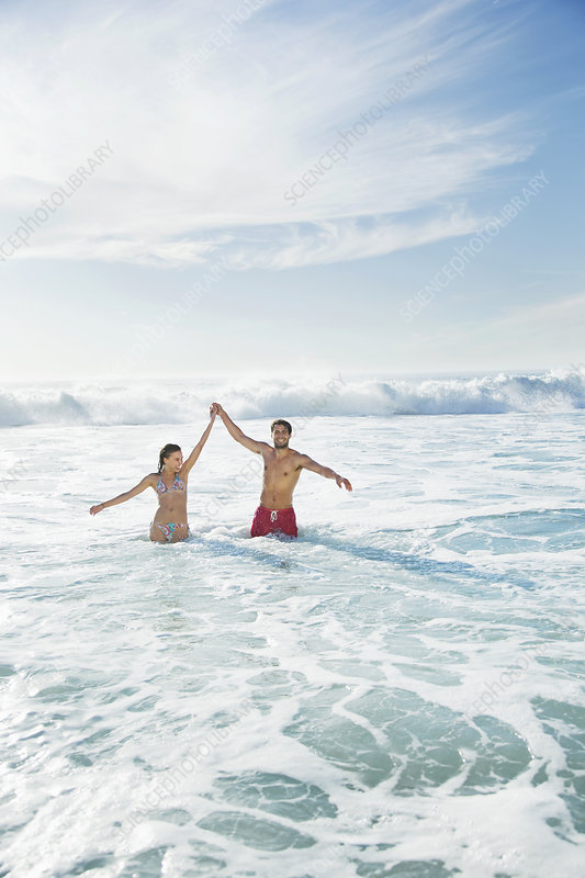 Couple standing in ocean with arms raised
