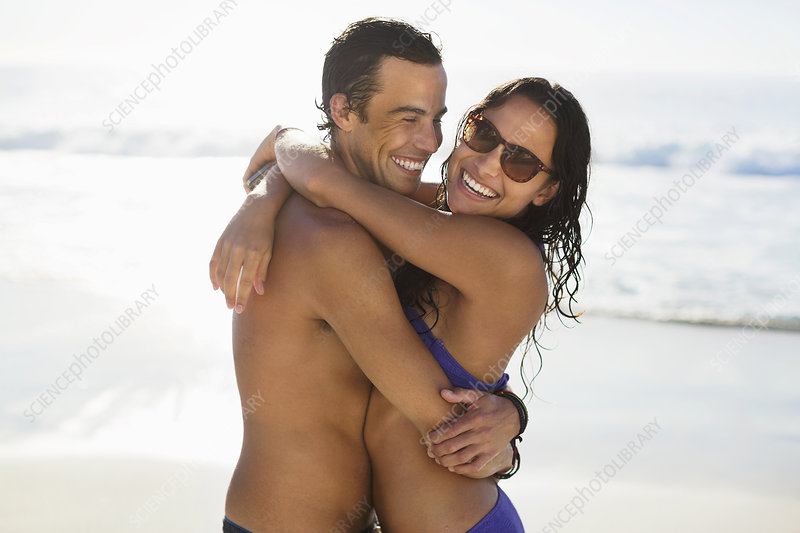 Portrait of happy couple hugging on beach