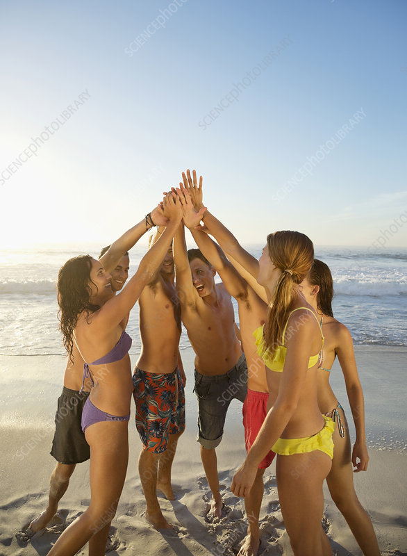 Friends high fiving in circle at beach