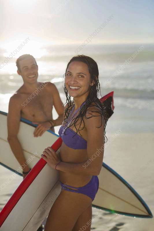 Happy couple holding surfboards on beach