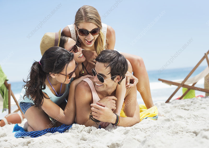 Happy friends laying on beach