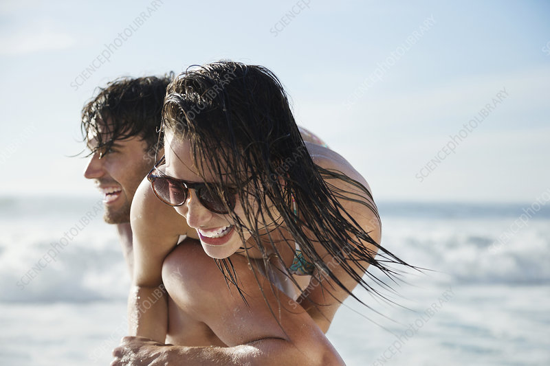 Man carrying enthusiastic woman on beach
