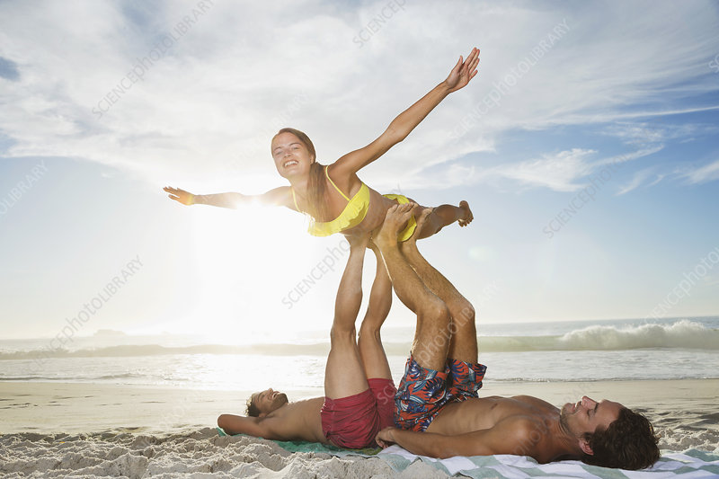 Men lifting woman with legs on beach