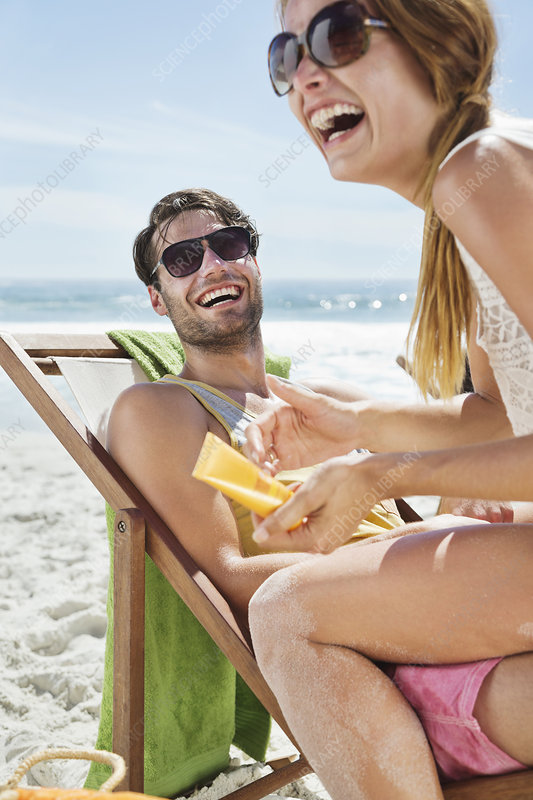 Happy couple with sunscreen at beach