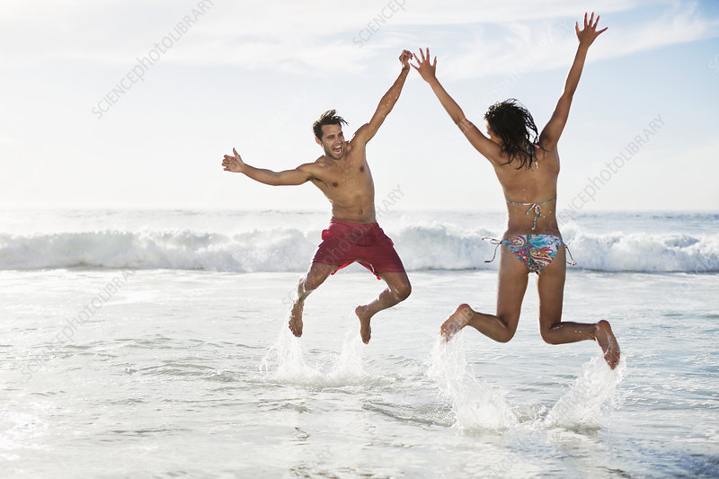Couple jumping with arms raised on beach